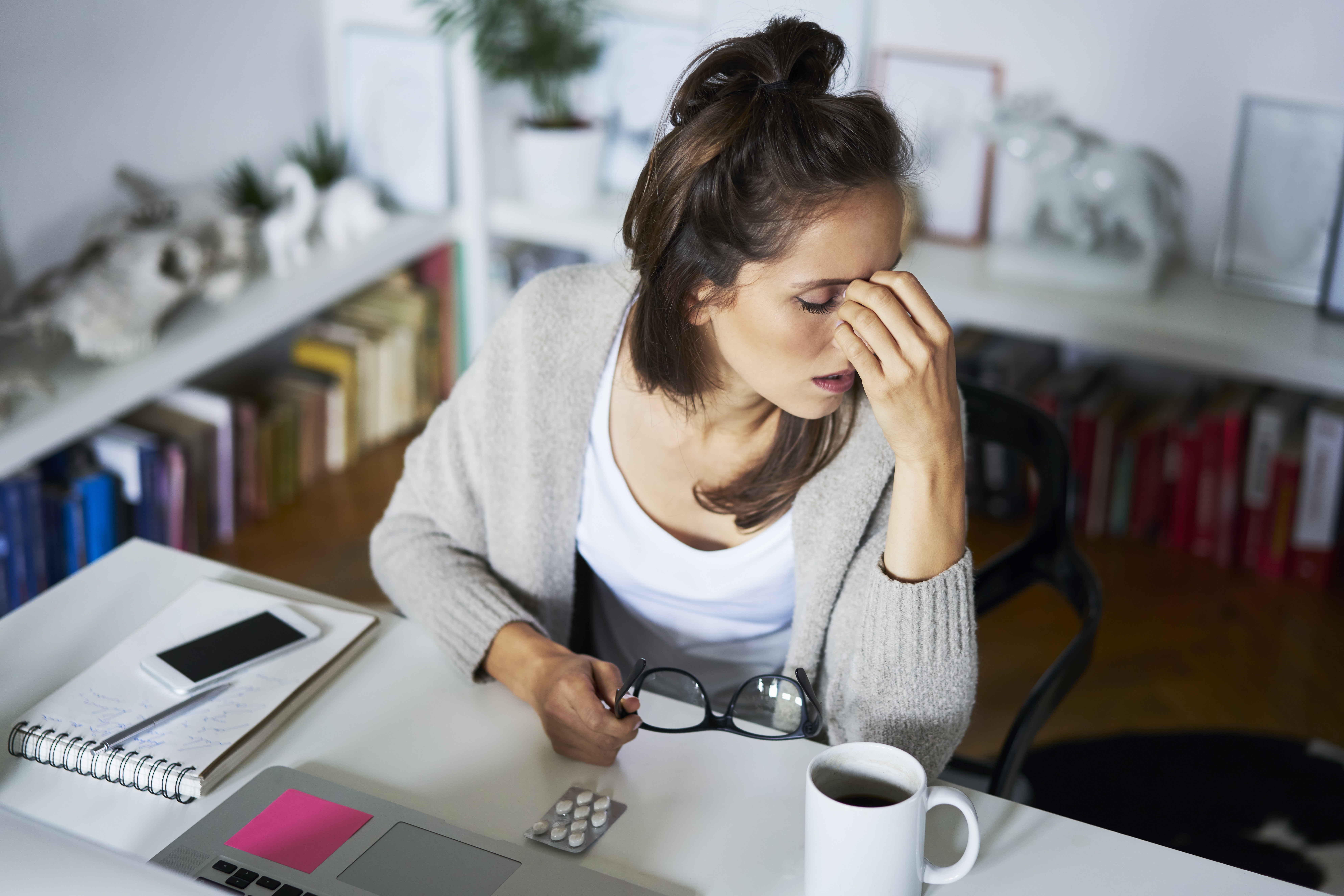 Stressed woman sitting at work desk