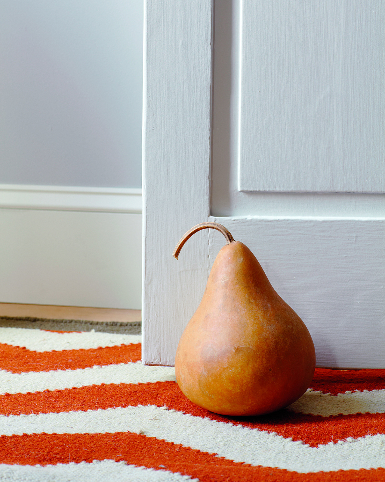 gourd placed door stopper on orange stripe carpet
