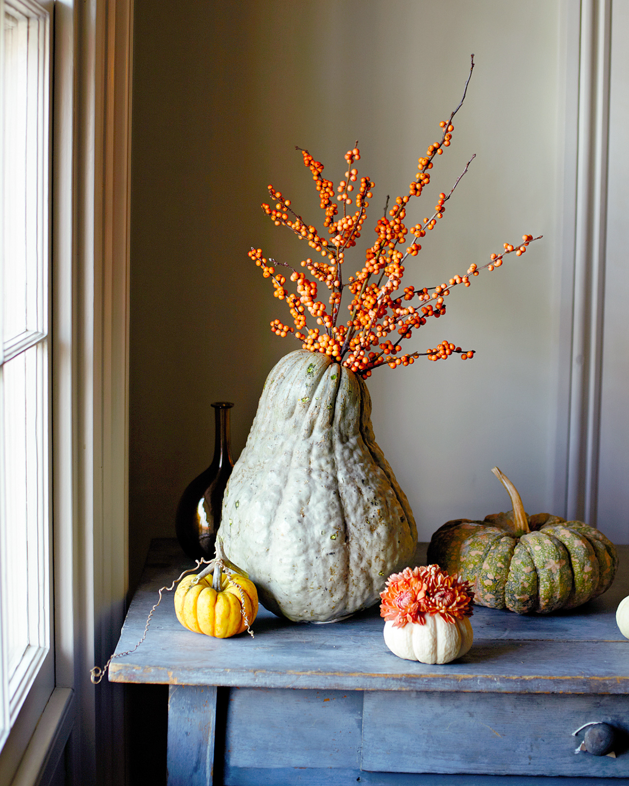 squash pumpkin fall floral arrangement near window