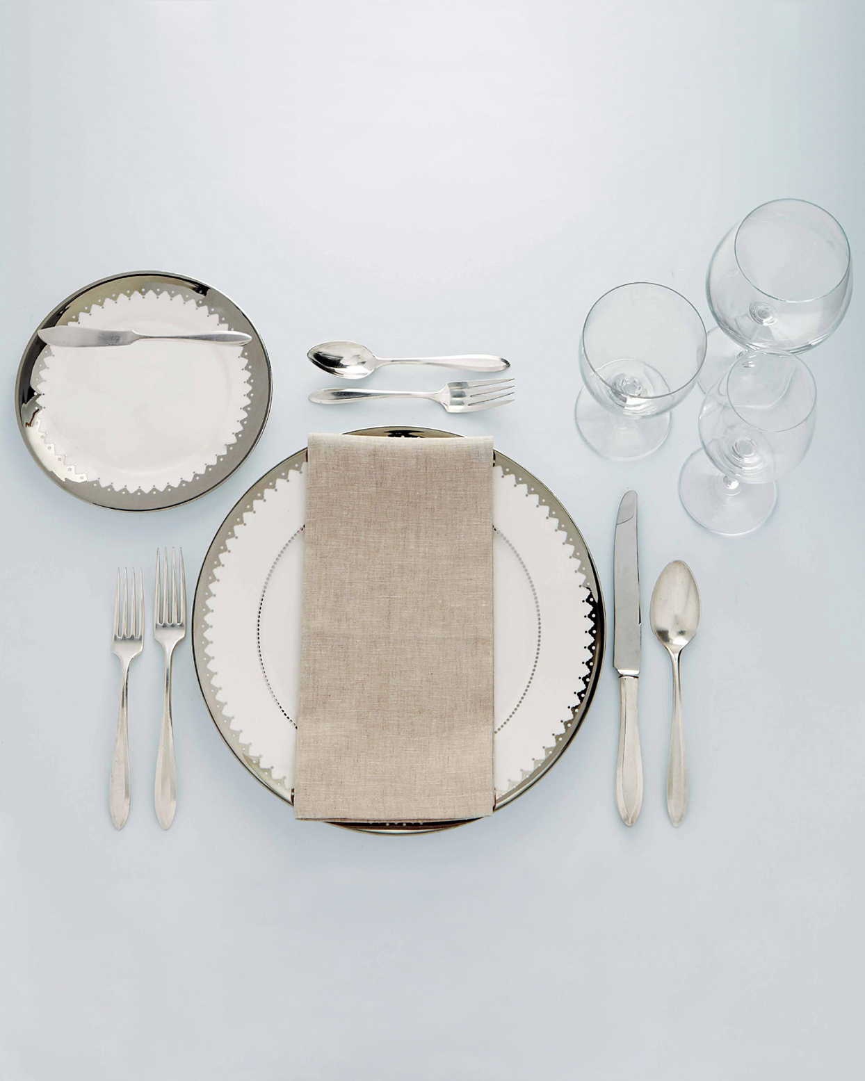 silver and white place setting on blue table