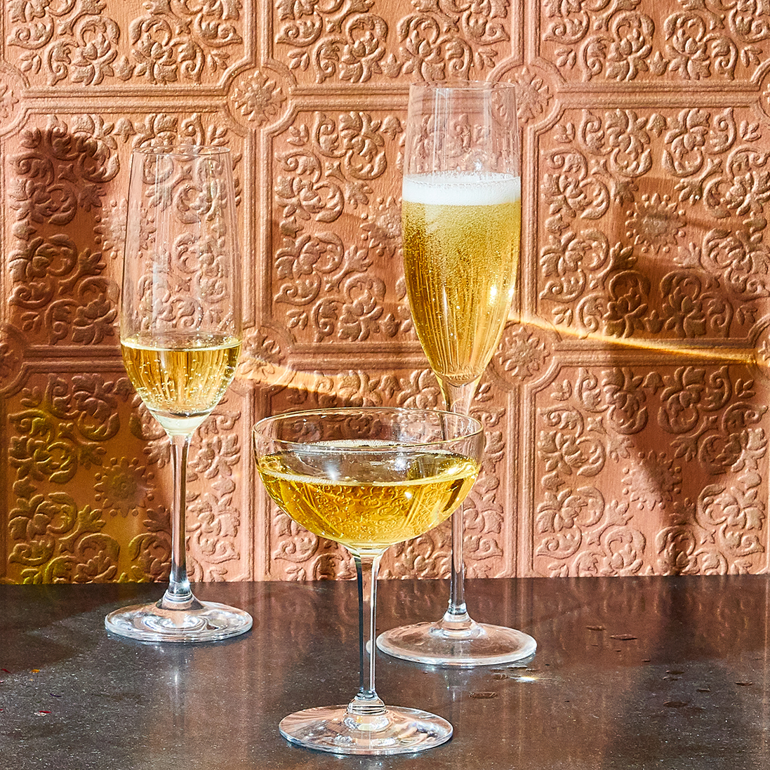 champagne glasses by metallic backsplash