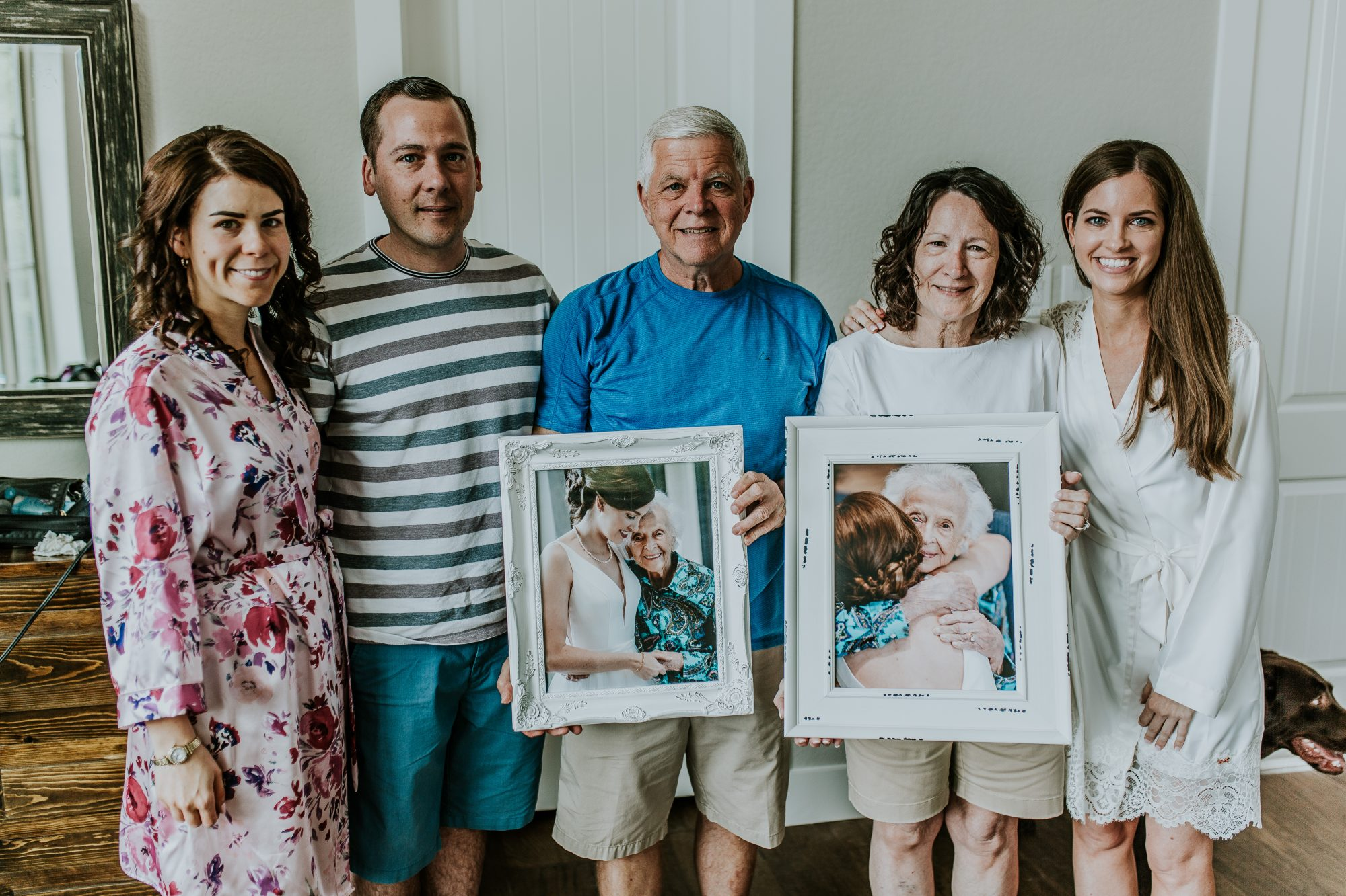 bride holding portraits of grandma with family