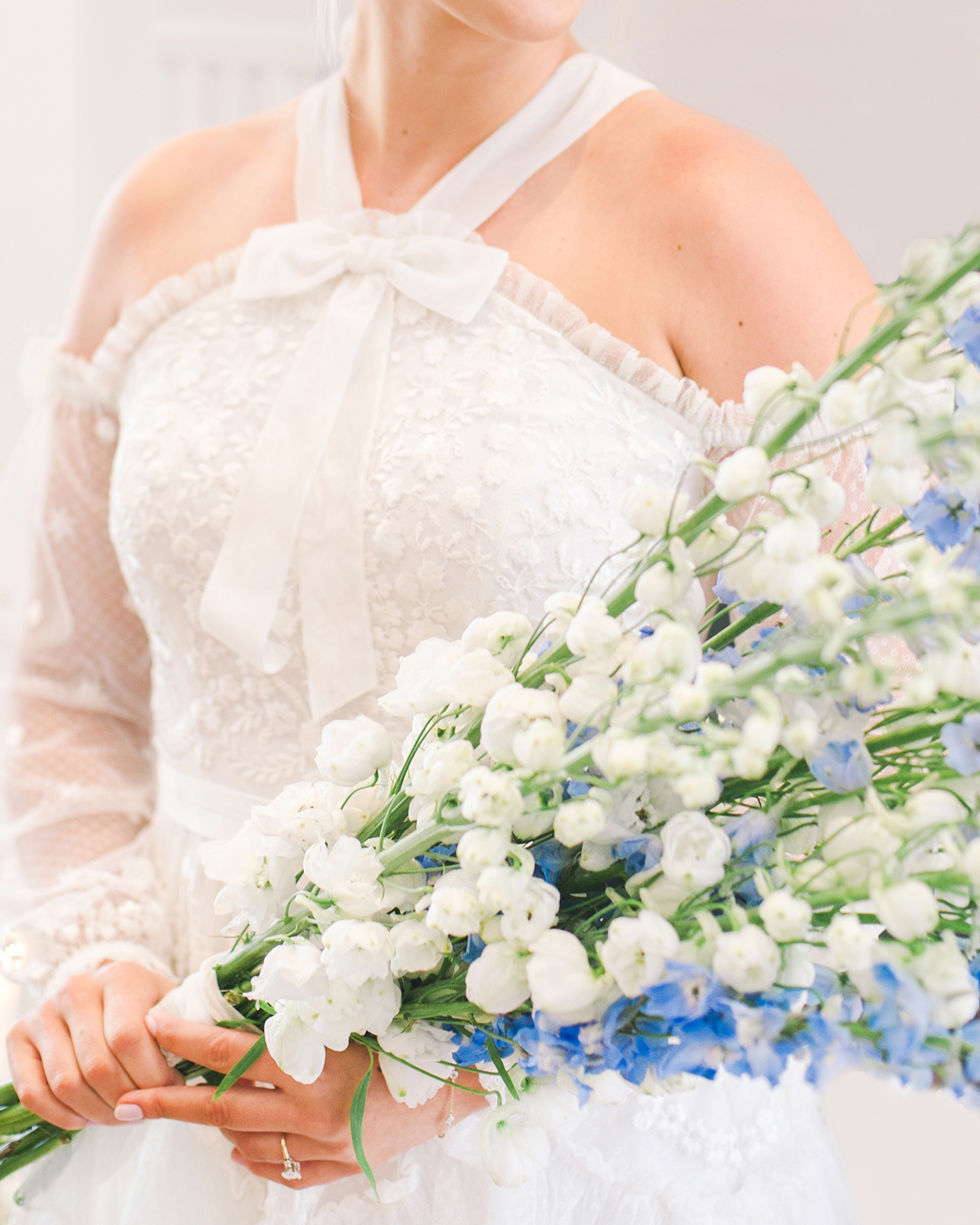 bride posing with blue white floral bouquet