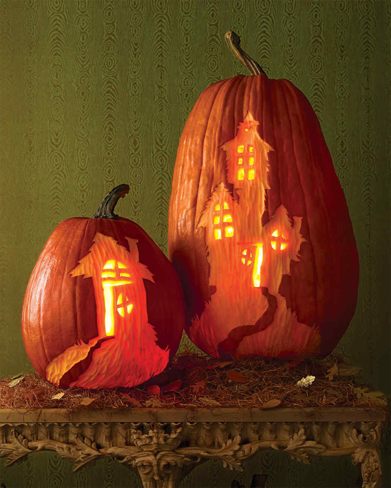 haunted houses carved on tall and short pumpkins