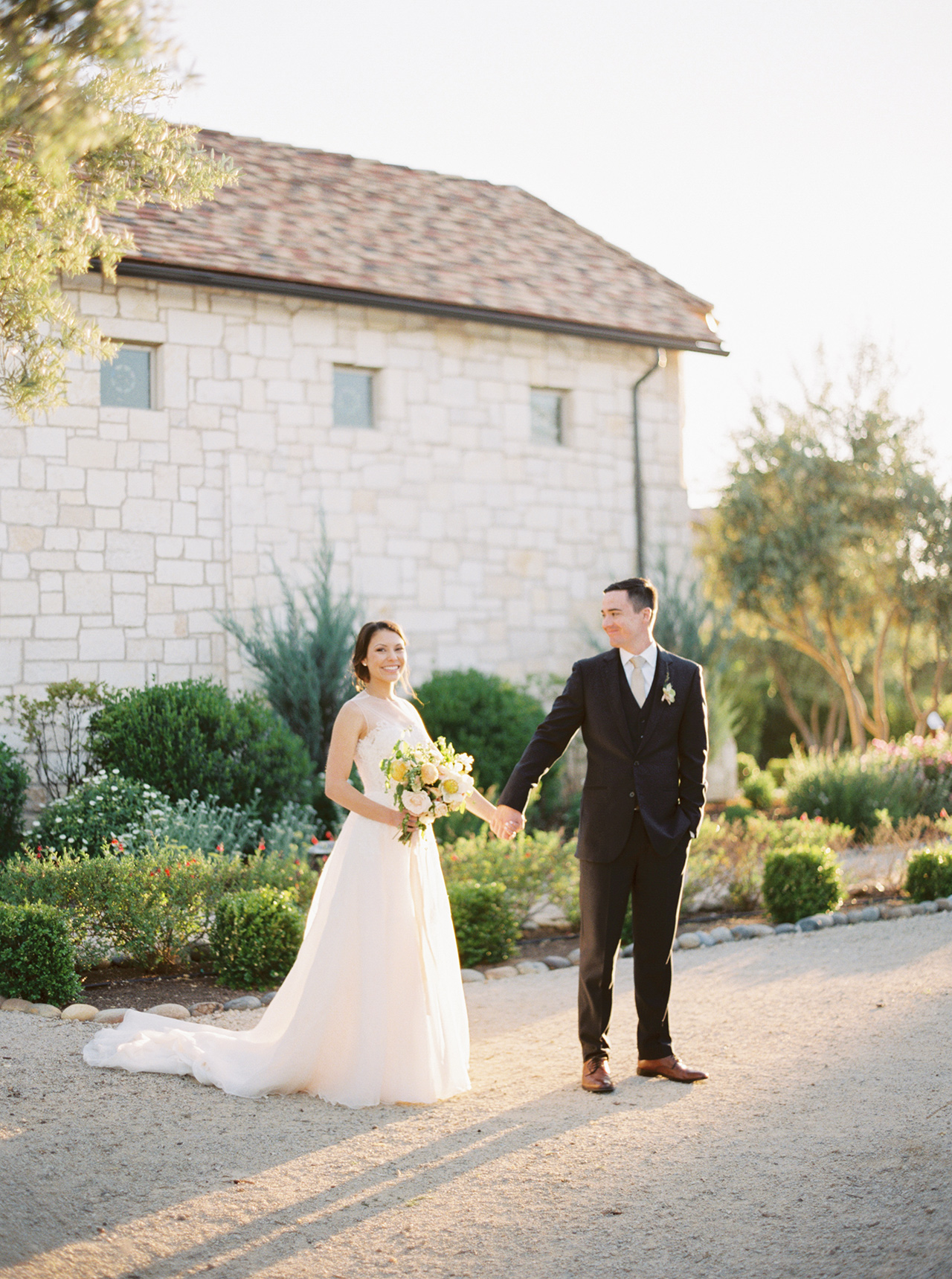 wedding couple hold hands outside tuscan building