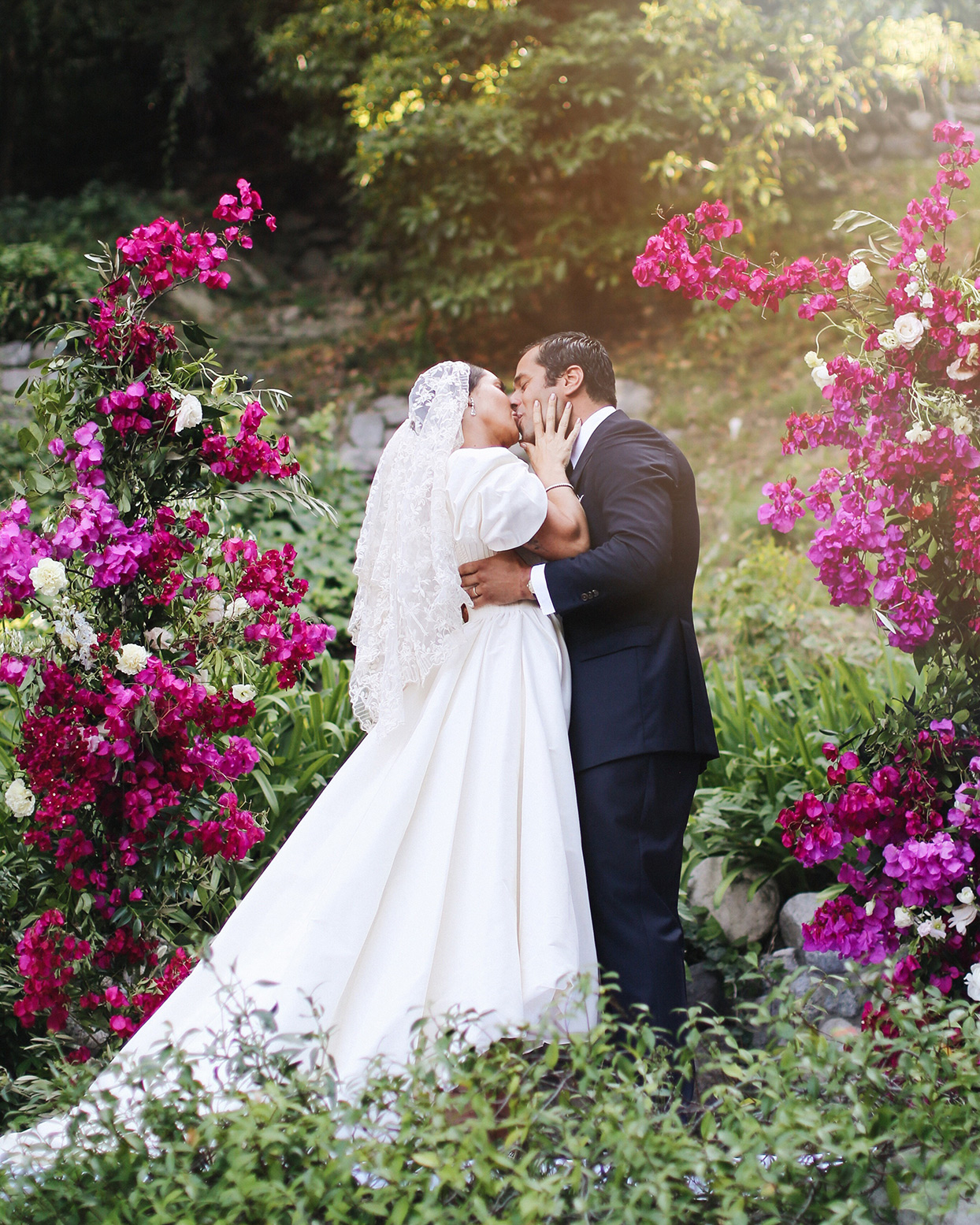 pia davide wedding ceremony kiss amongst fuchsia flowers