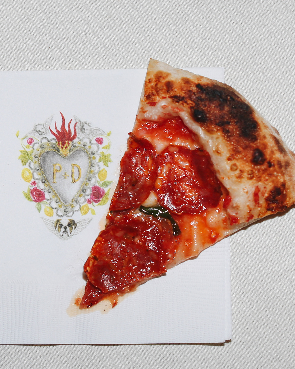 pia davide wedding pizza slice on napkin with crest