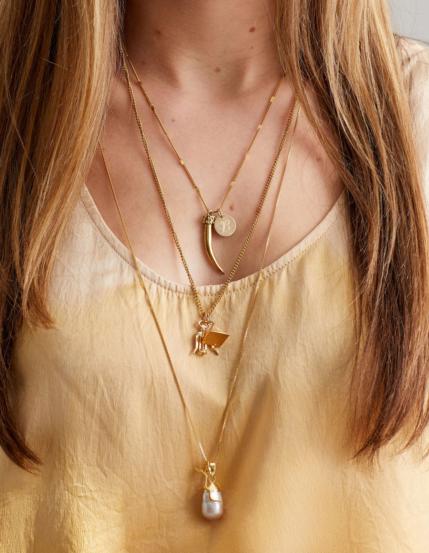 woman wearing three layered necklaces