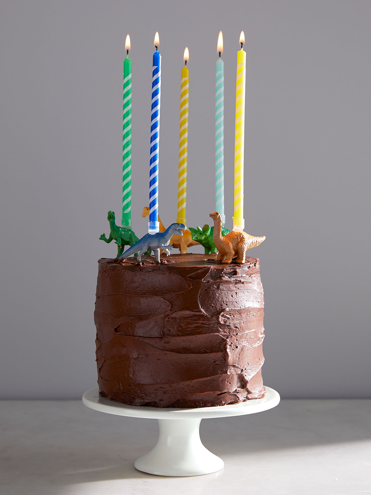 chocolate birthday cake decorated with candles and dinosaurs