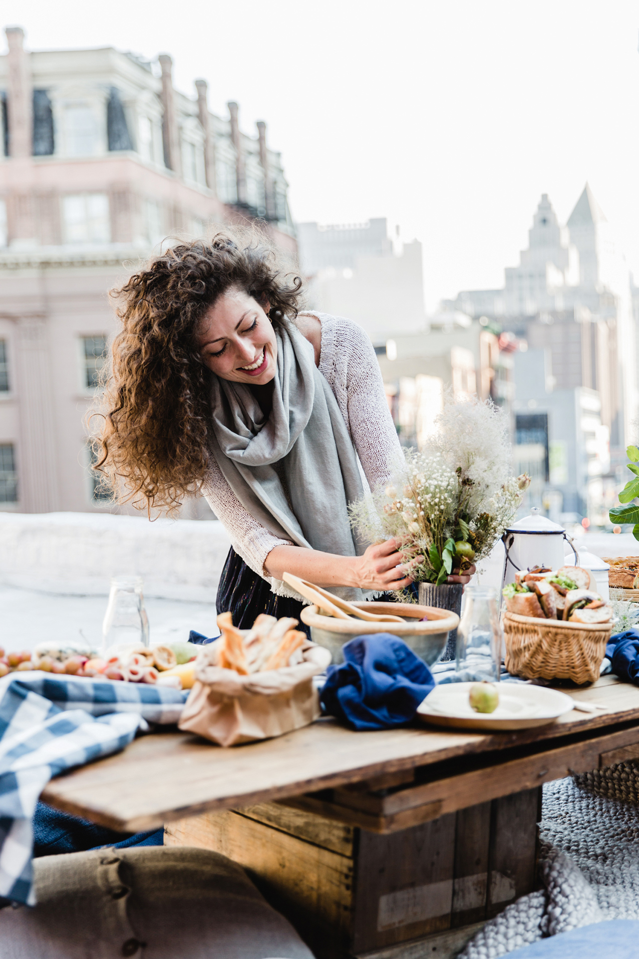 woman working with floral arrangement rooftop picknic