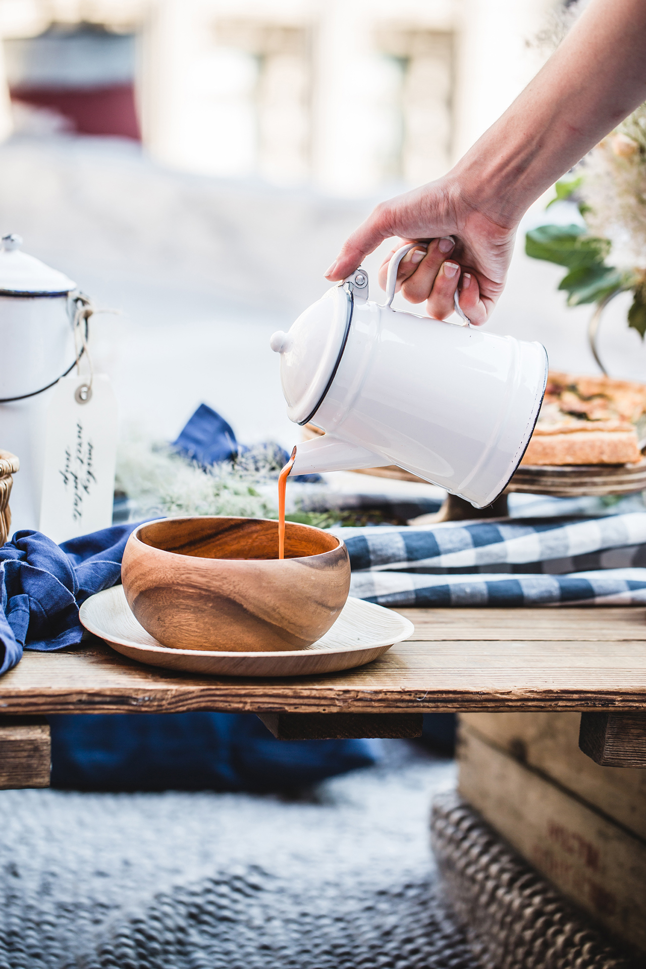 serving soup with kettle into wooden bowl rooftop picnic