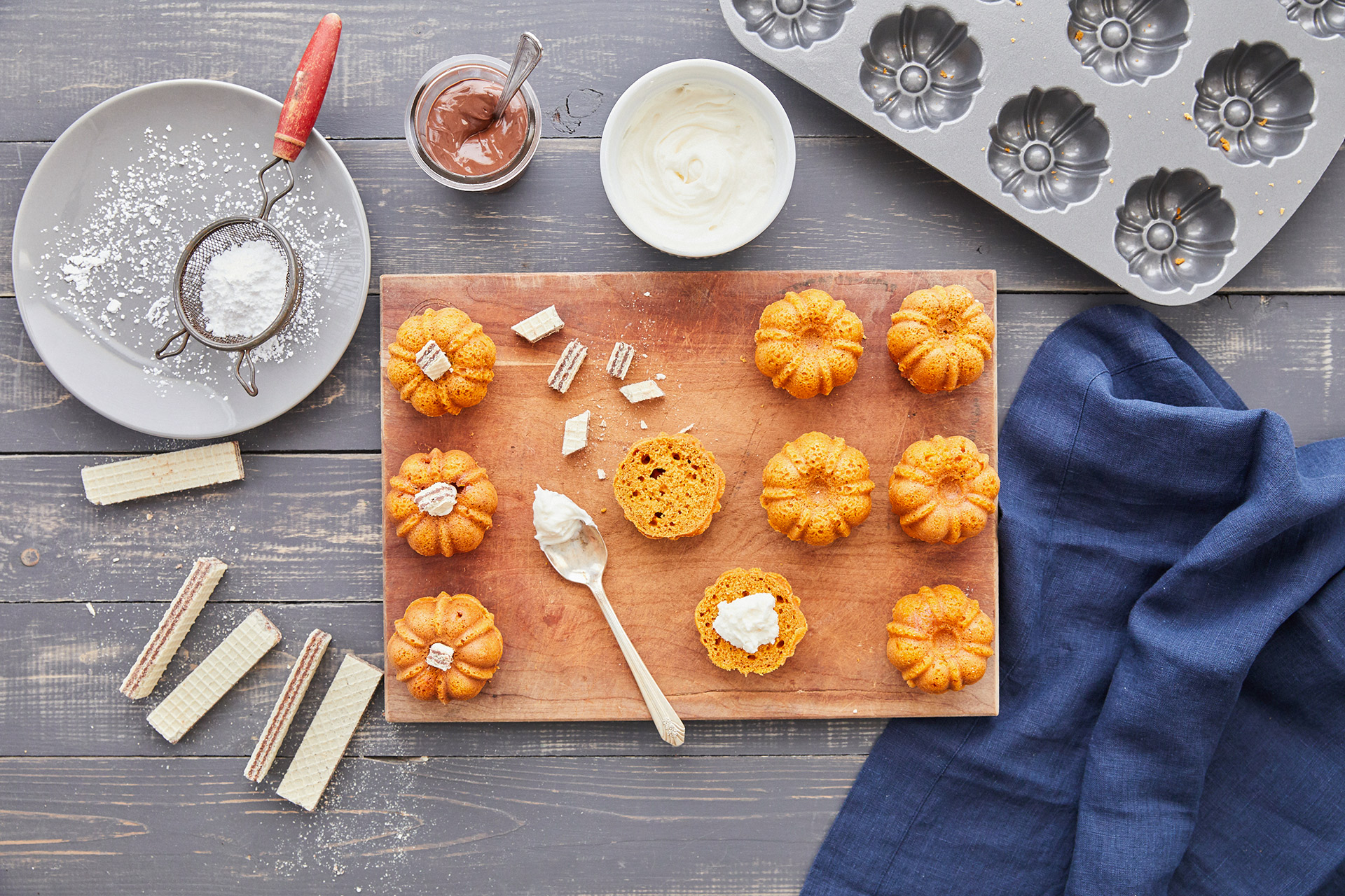 adding cookies and cream to mini pumpkin bundt cakes