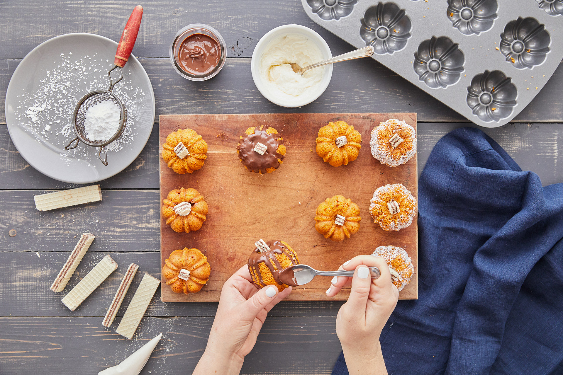 adding chocolate topping mini pumpkin bundt cakes