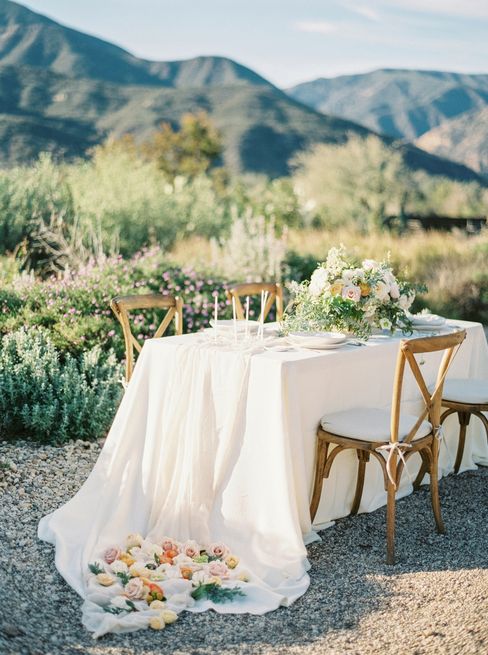 intimate reception table outdoors flowing white tablecloth roses