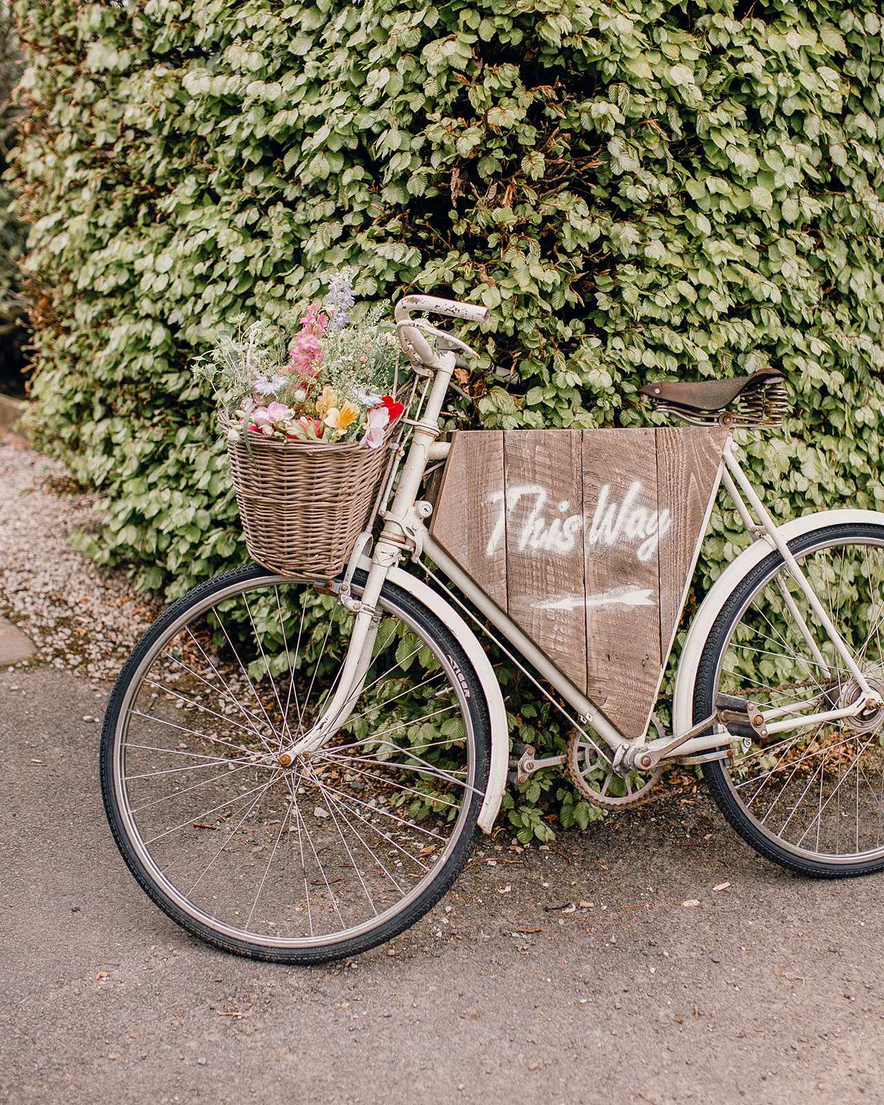 rustic bike directional sign with floral basket