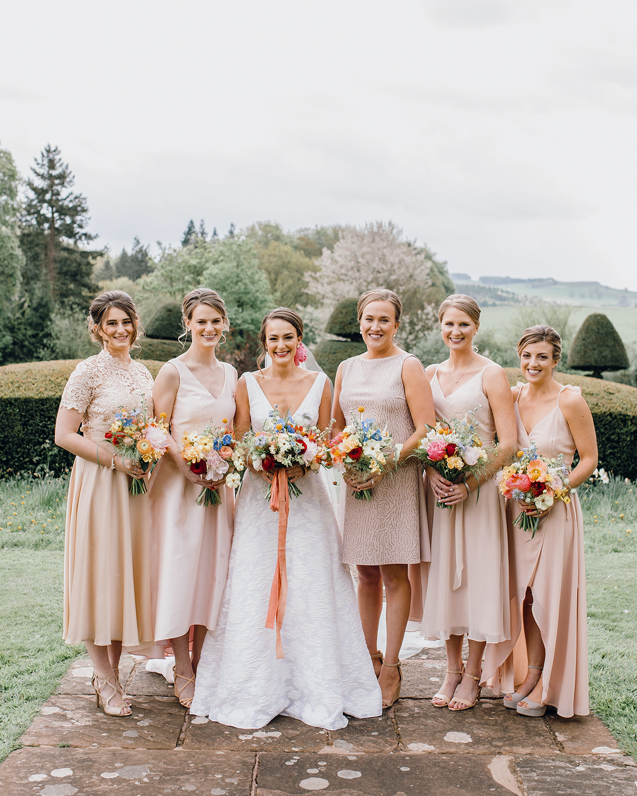 bride posing with bridesmaids in blush dresses