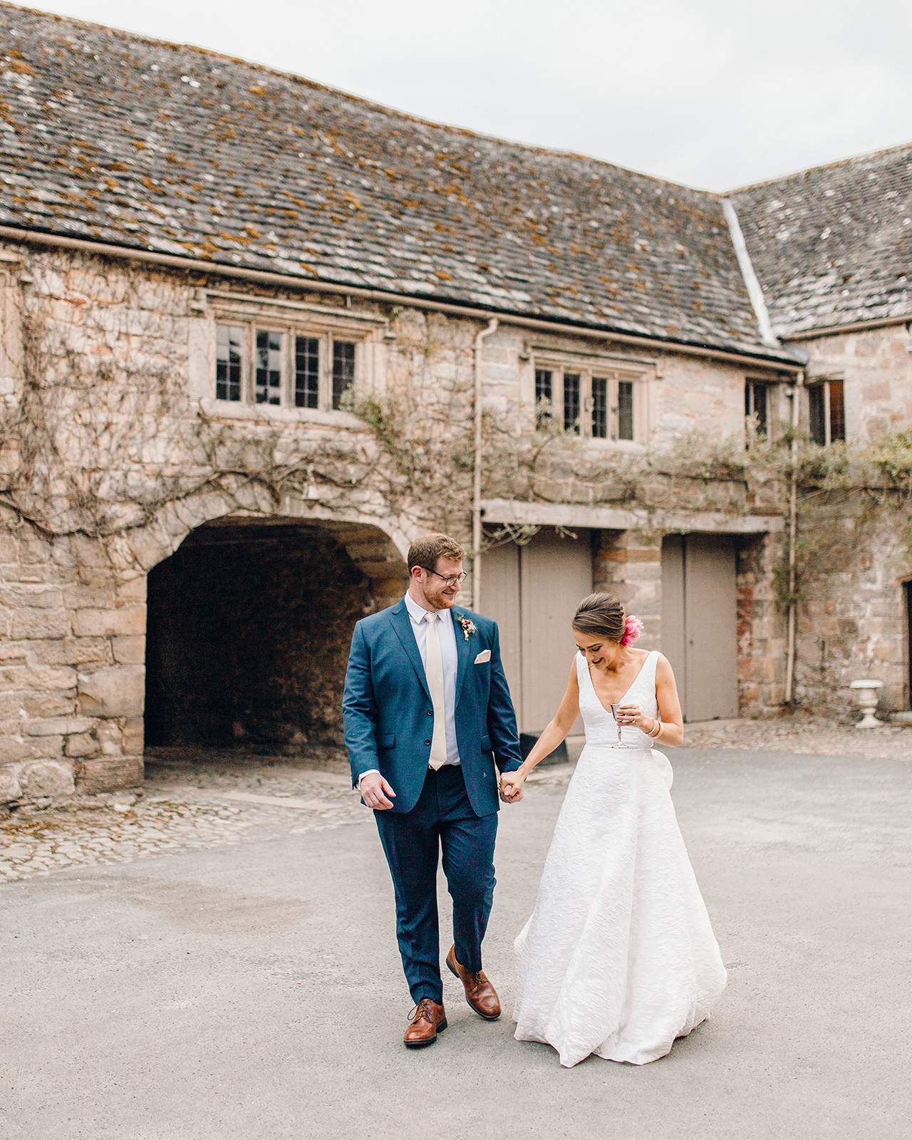 wedding couple walking outside of rustic building