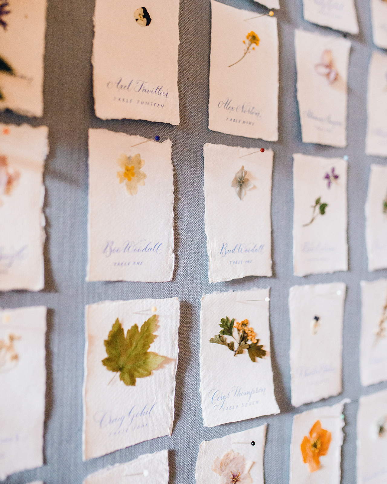 escort card wall with pressed flowers