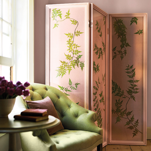 A pink room divider with green pressed leaves.