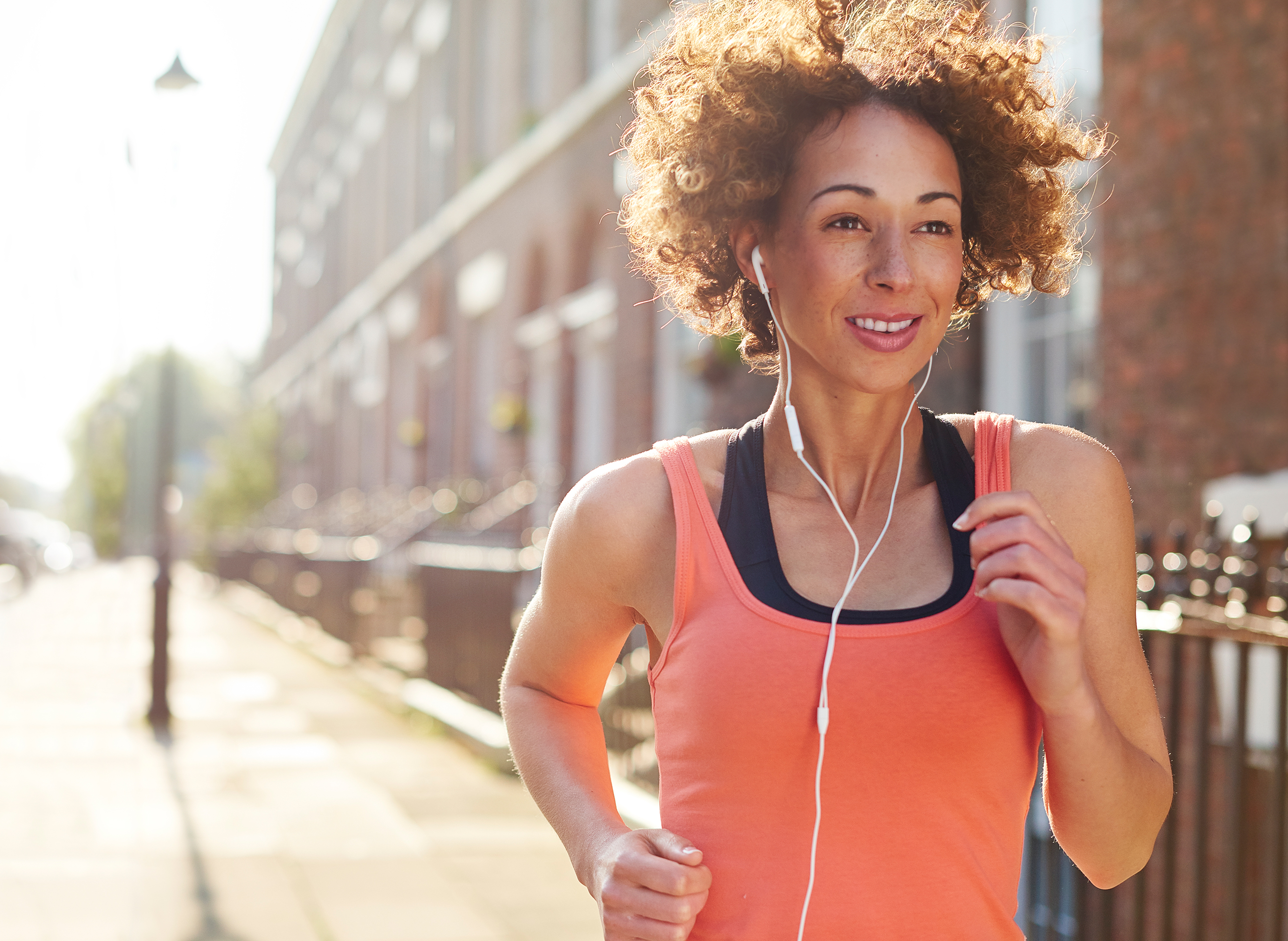 A woman is jogging in the morning in a city.