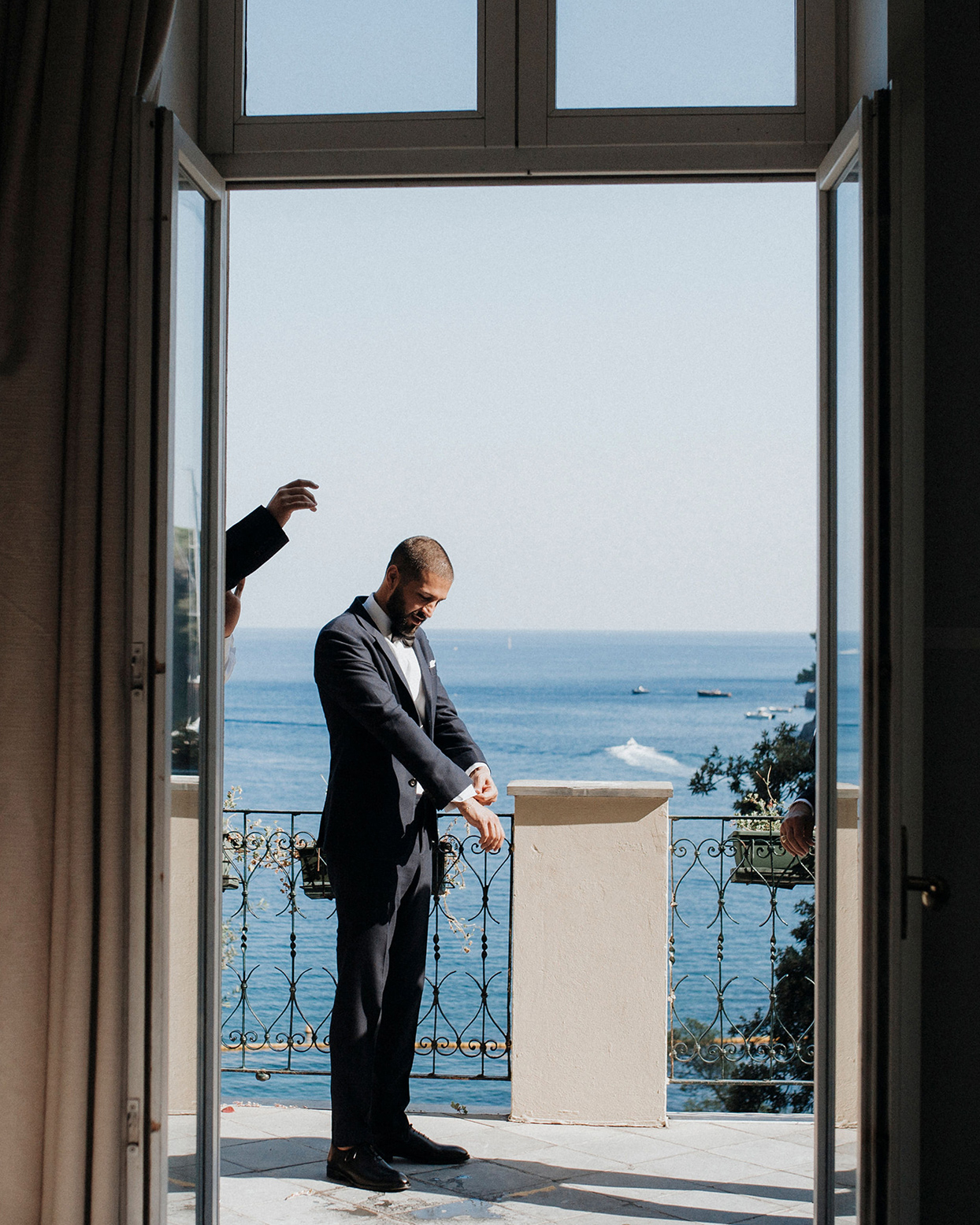 jaclyn antonio wedding groom getting ready overlooking water