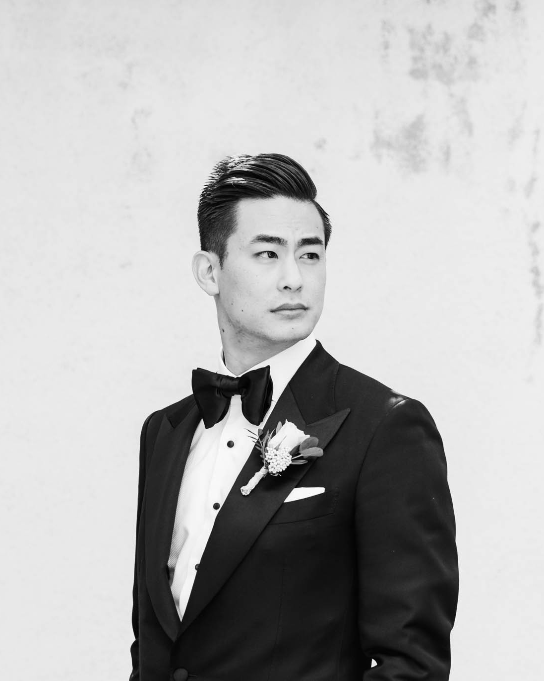 groom poses in black tuxedo and bow tie