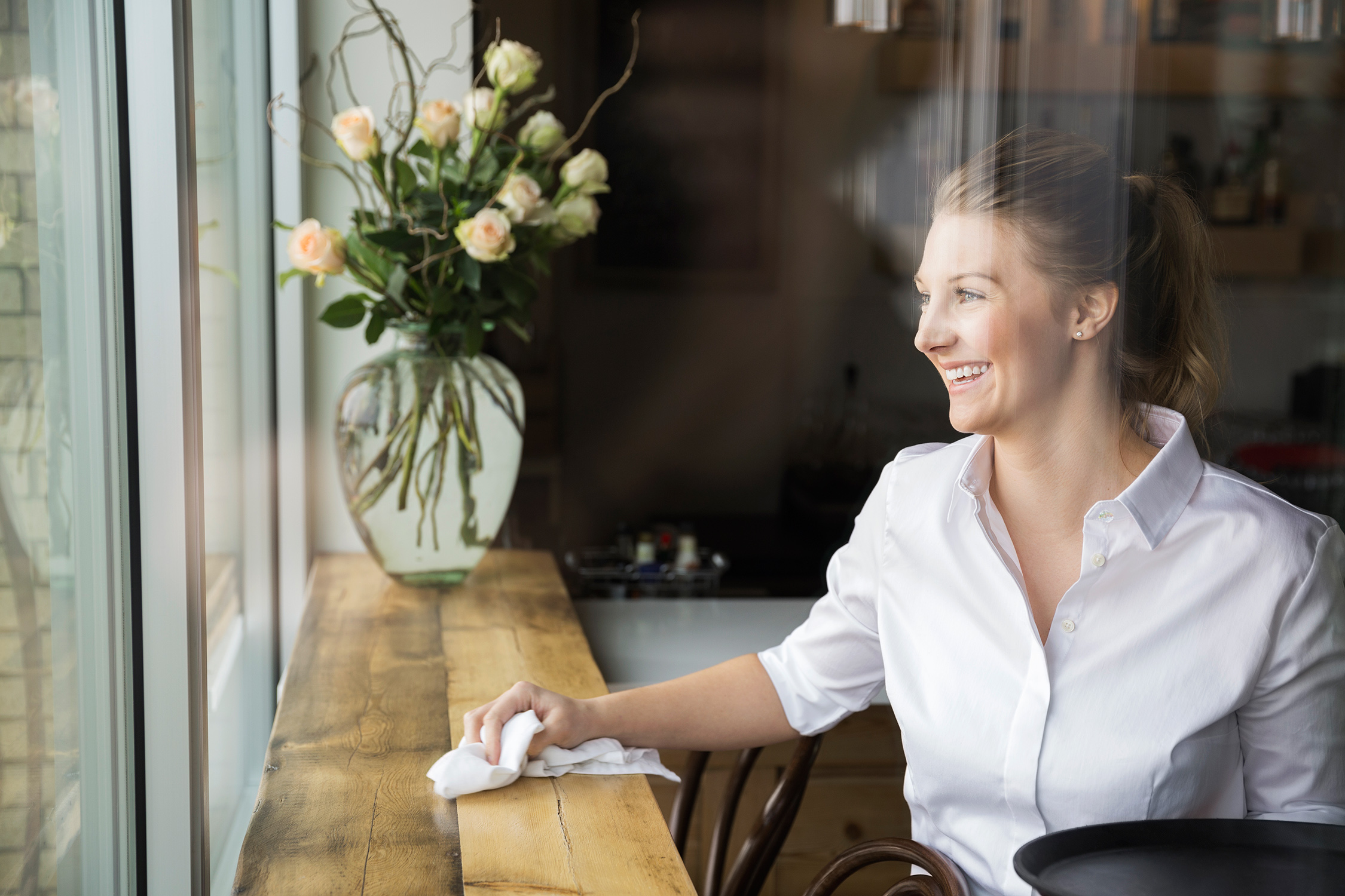 Waitress wiping counter and looking out window