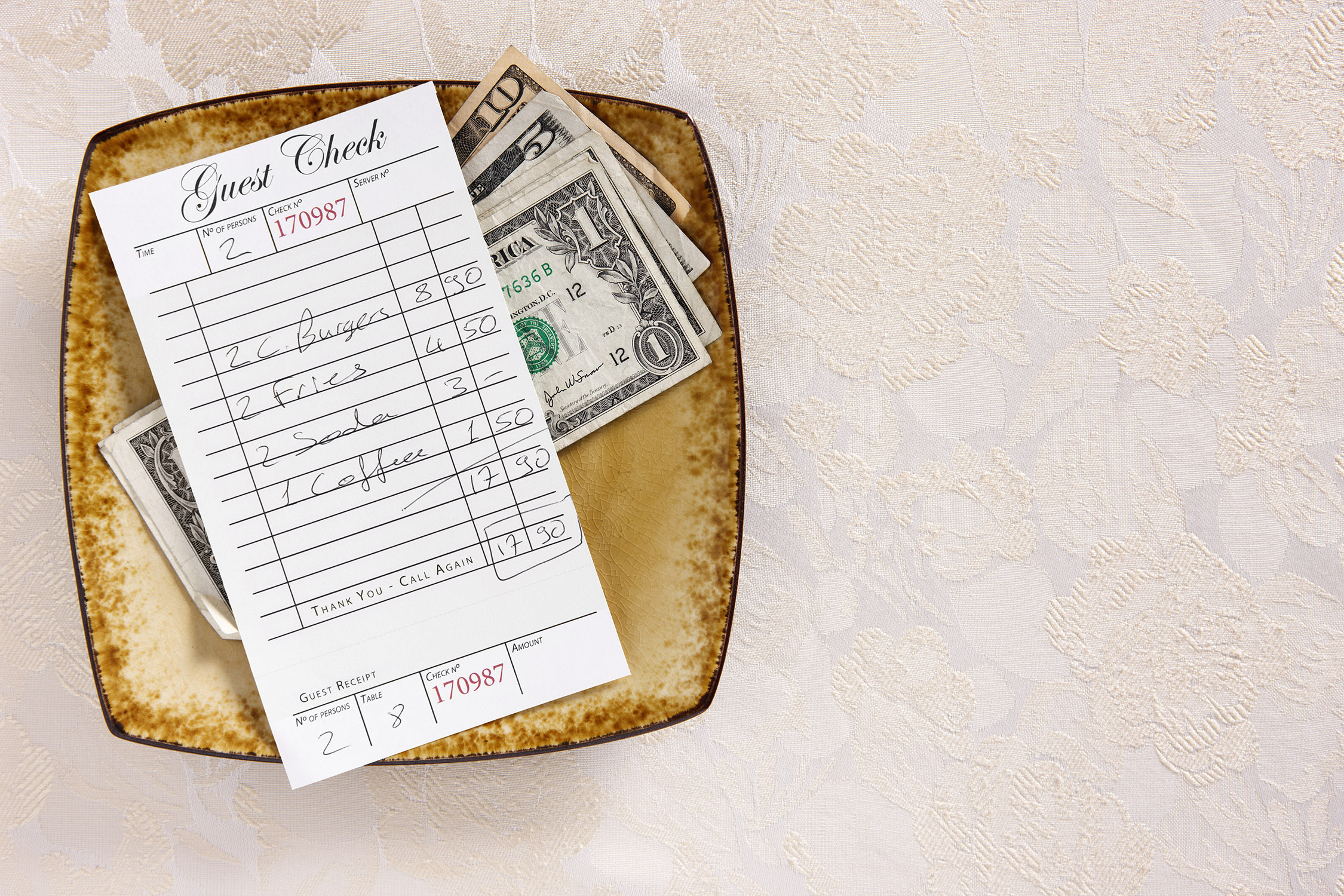 Guest check on the tip plate in a restaurant with US Dollars