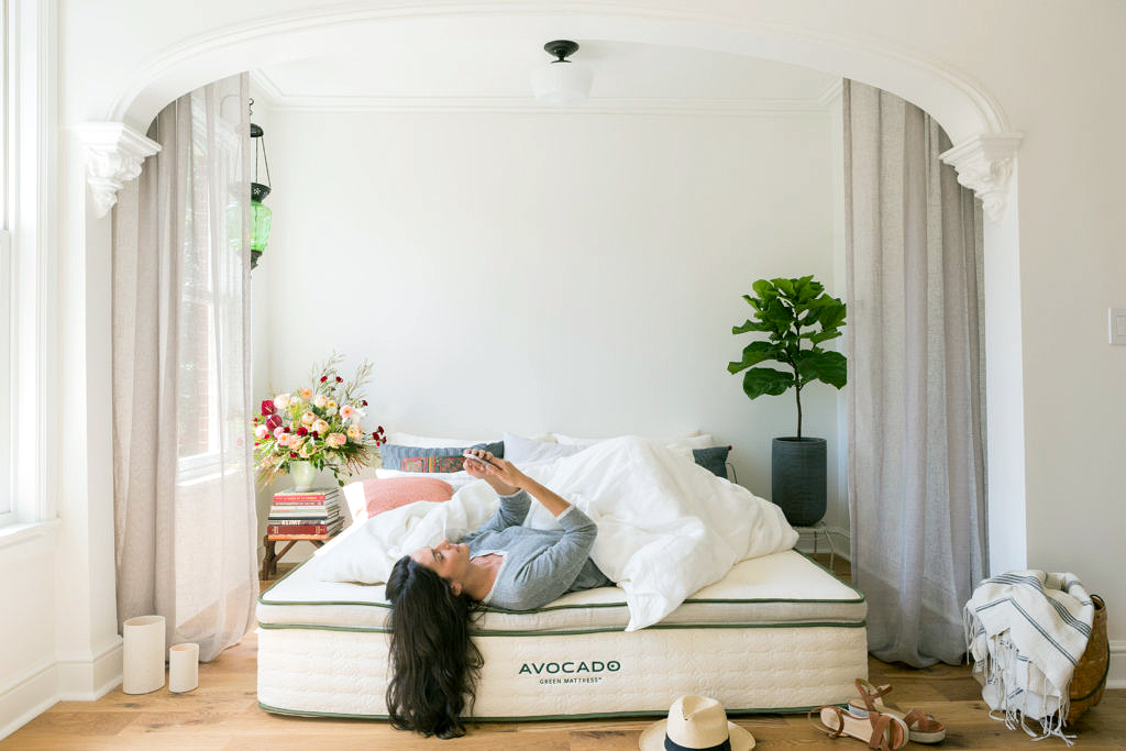 woman lying on avocado green mattress in bedroom