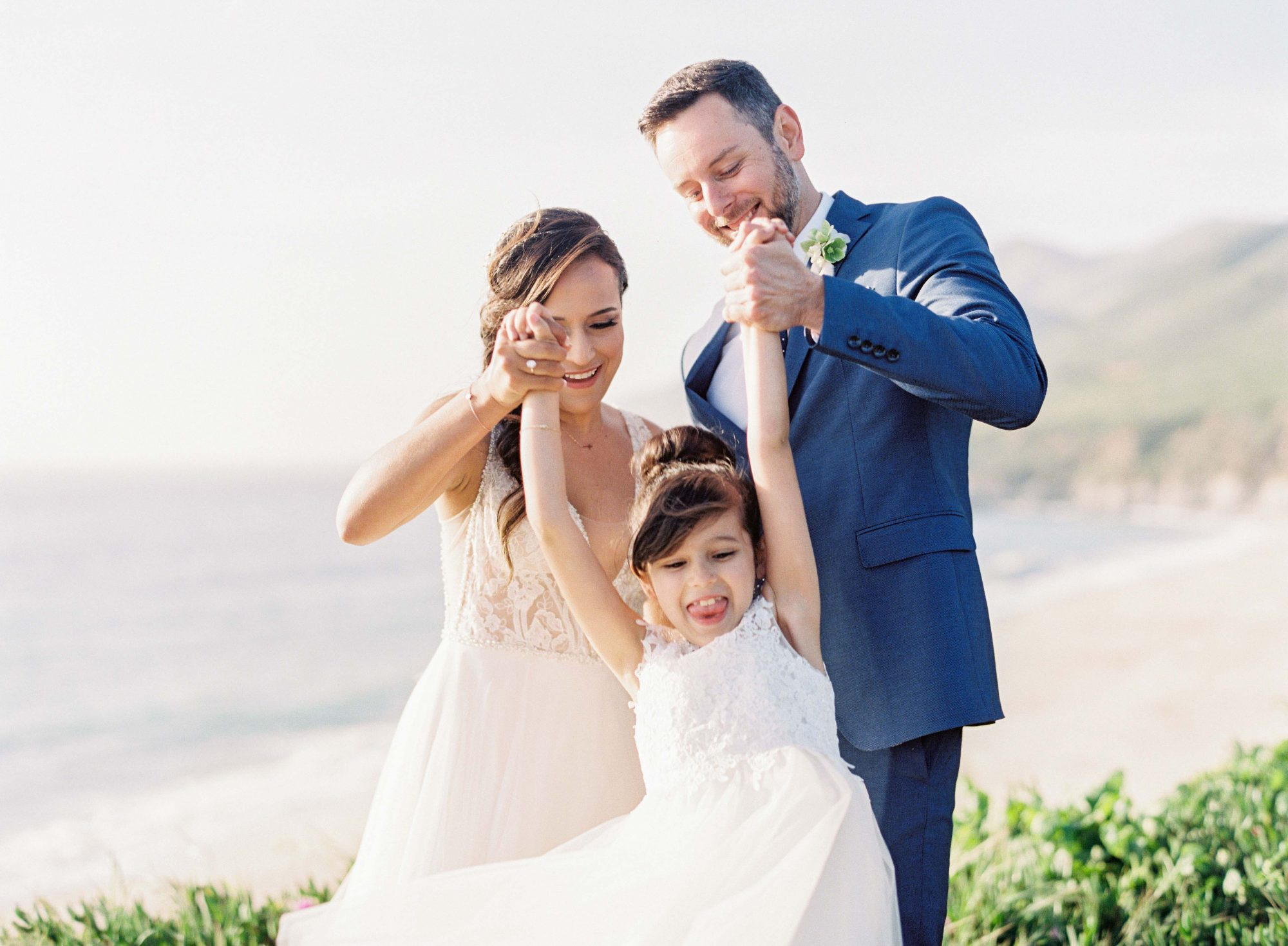 bride and groom hold hands with girl outside