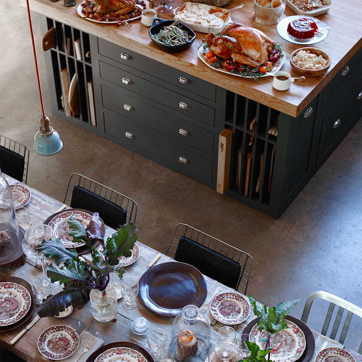 overhead view of long table and kitchen island with thanksgiving food