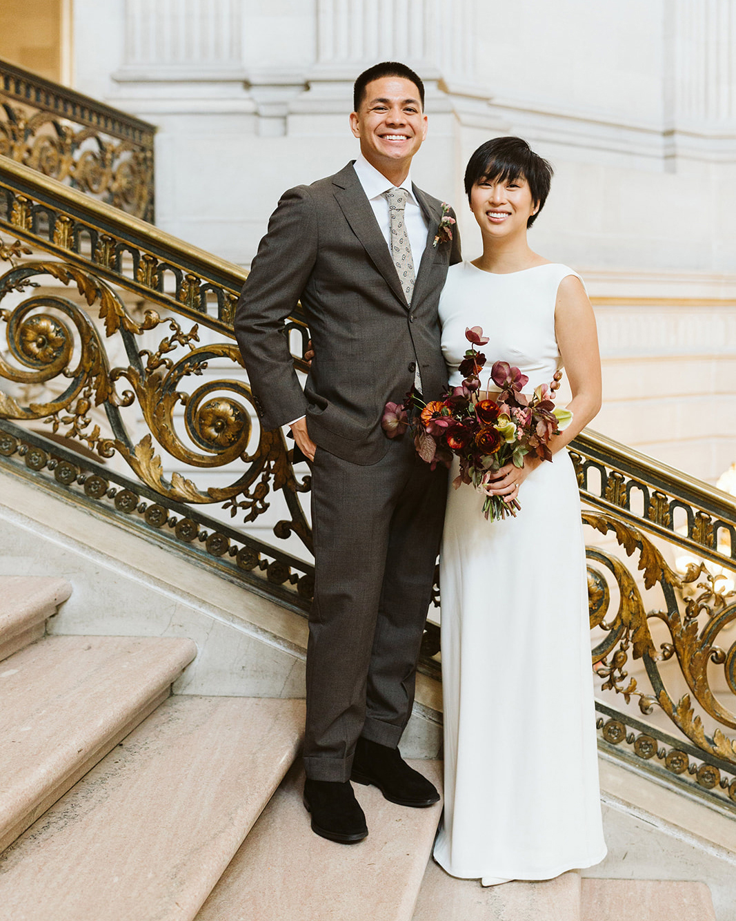 bride groom pose on stairway decorative gold railing