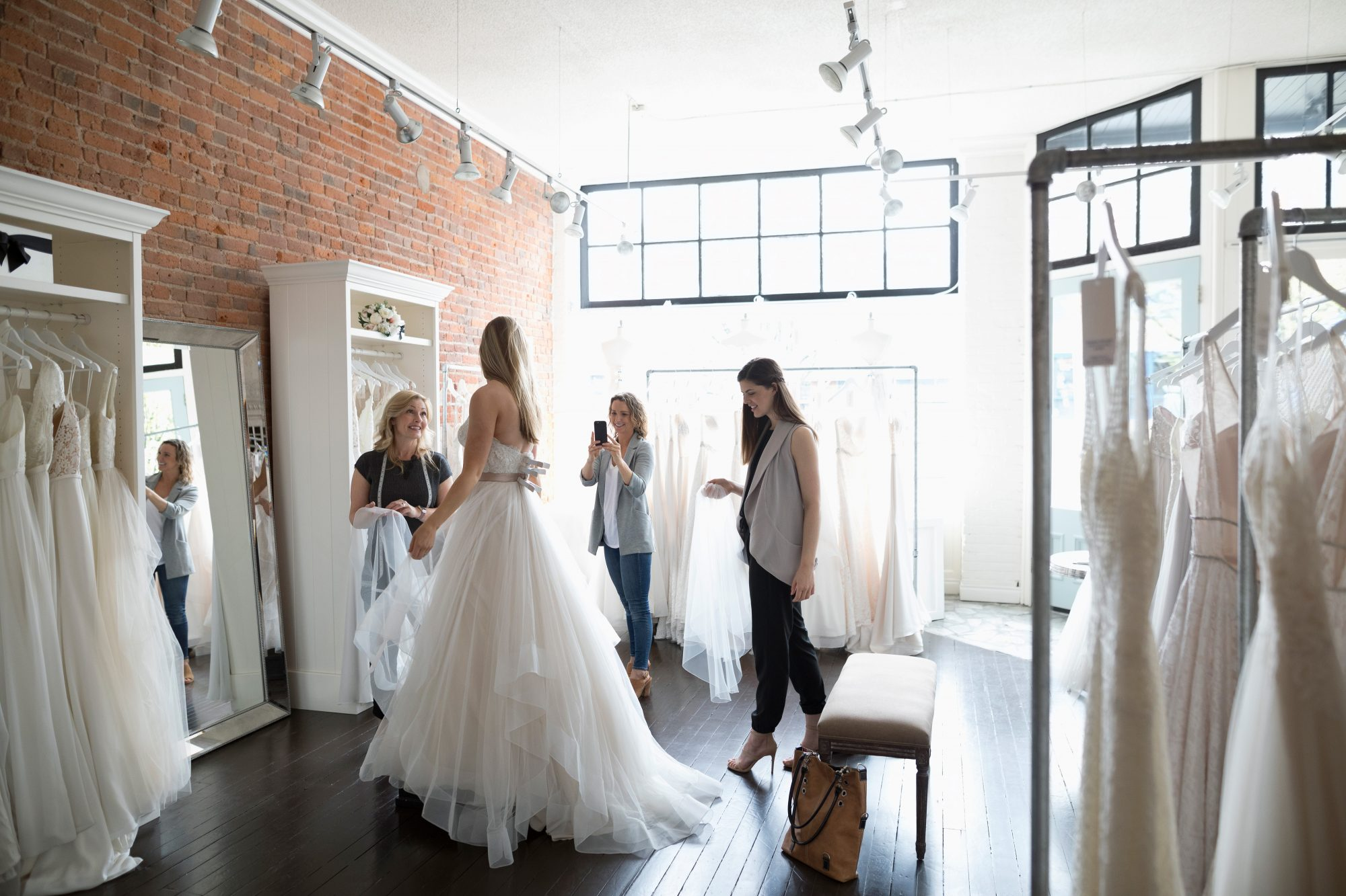 Woman Trying on Wedding Dress at Bridal Salon with Friends