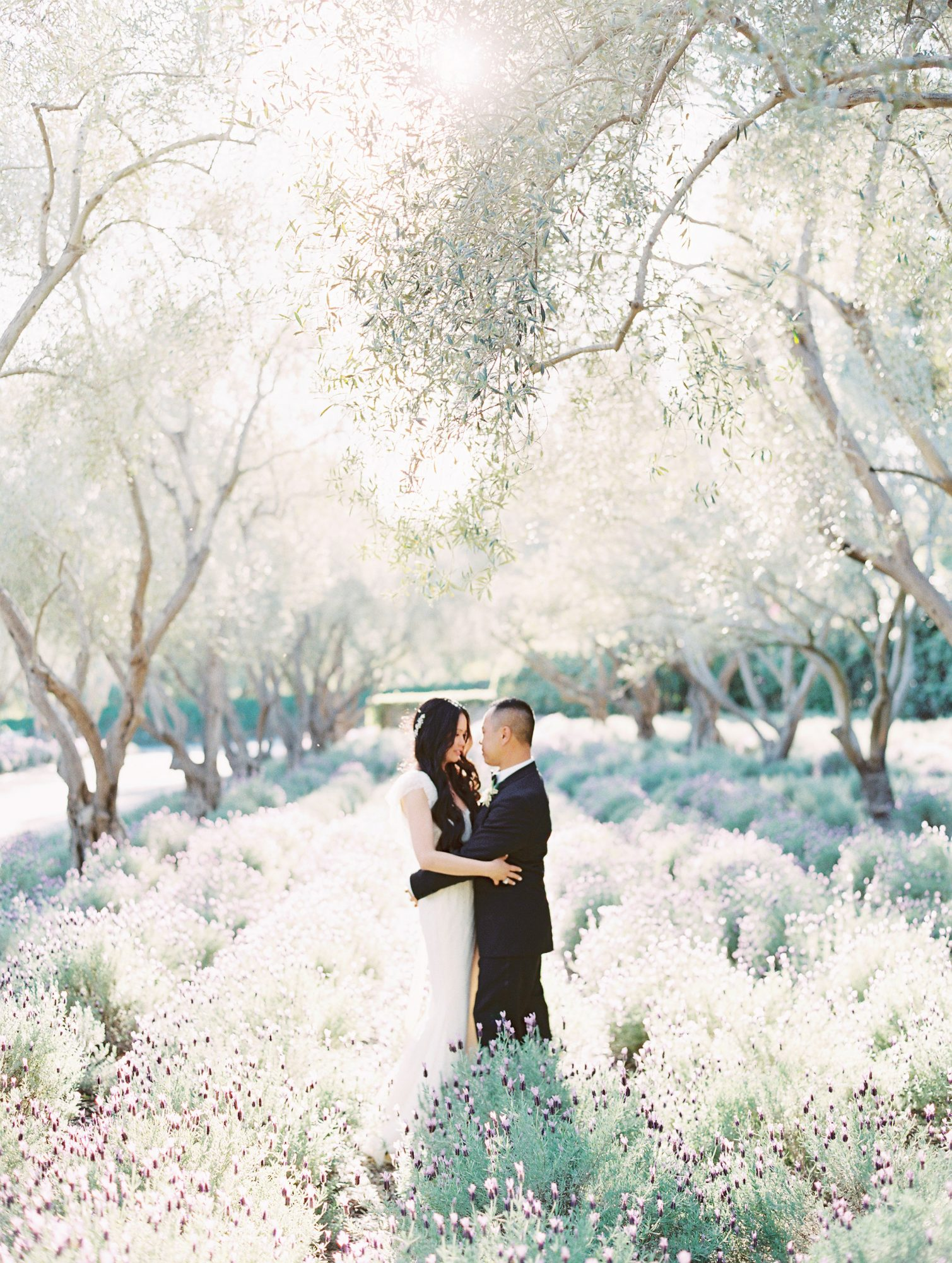 bride and groom standing under tree surrounded by flowers