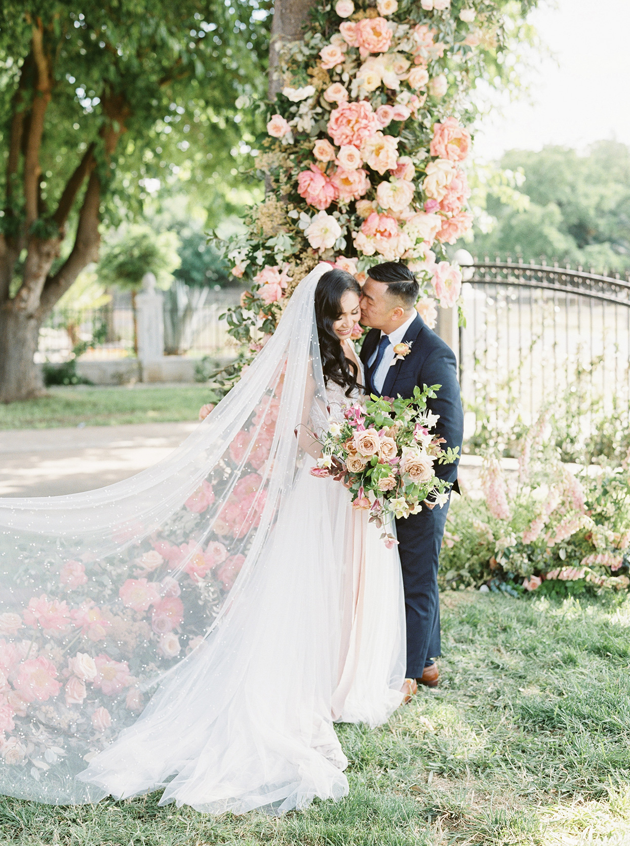 thuy kahn wedding couple in front of floral garland