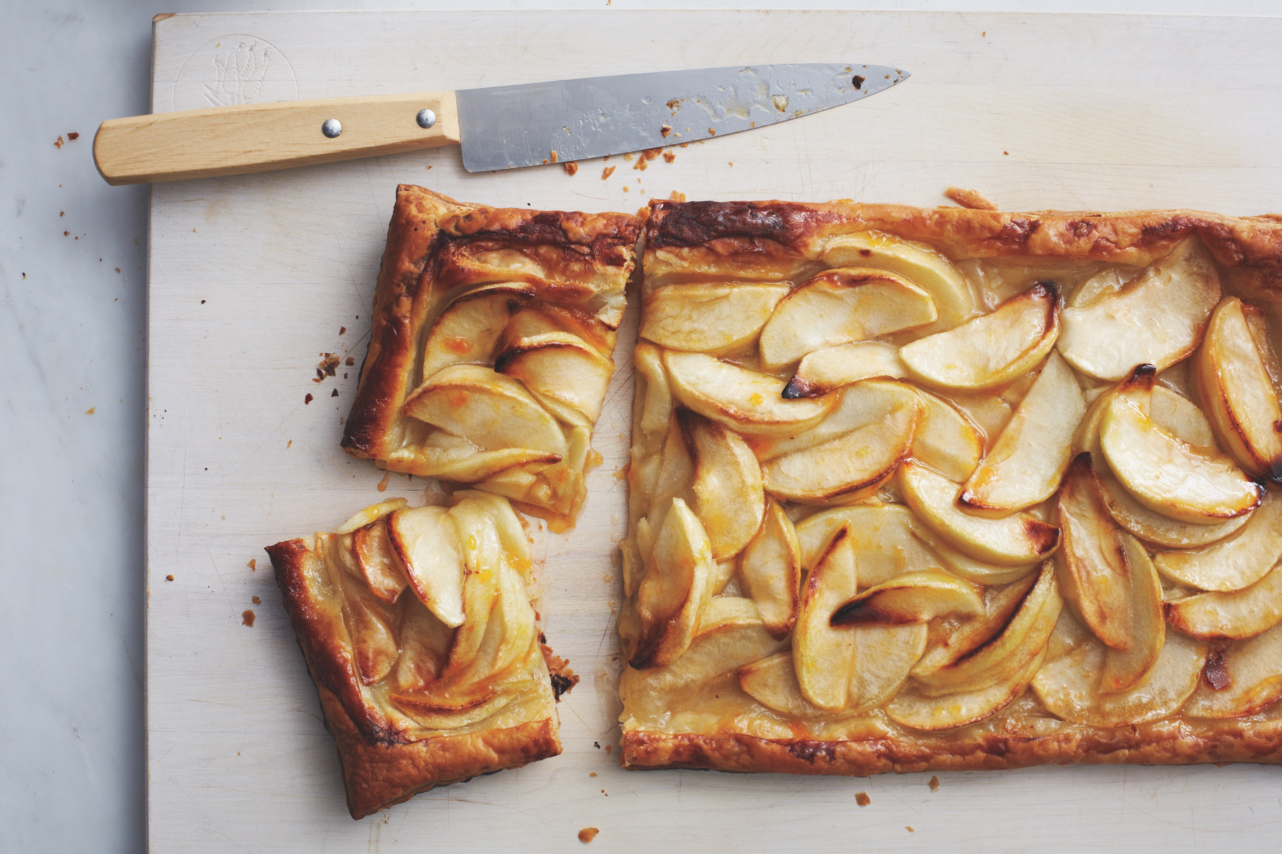 apple tart puff pastry dessert on cutting board with knife
