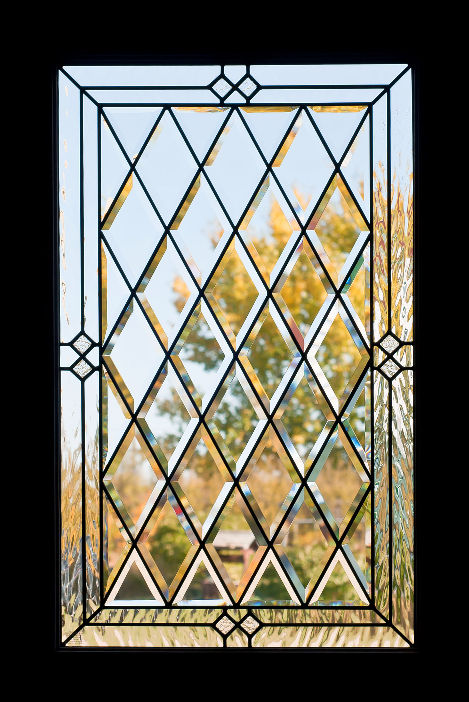 A door window with beveled glass diamond shapes looking outside