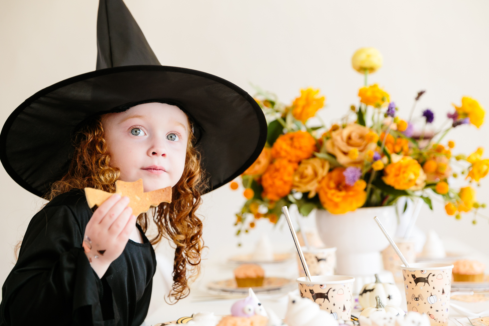 little girl in a witch costume eating cookies