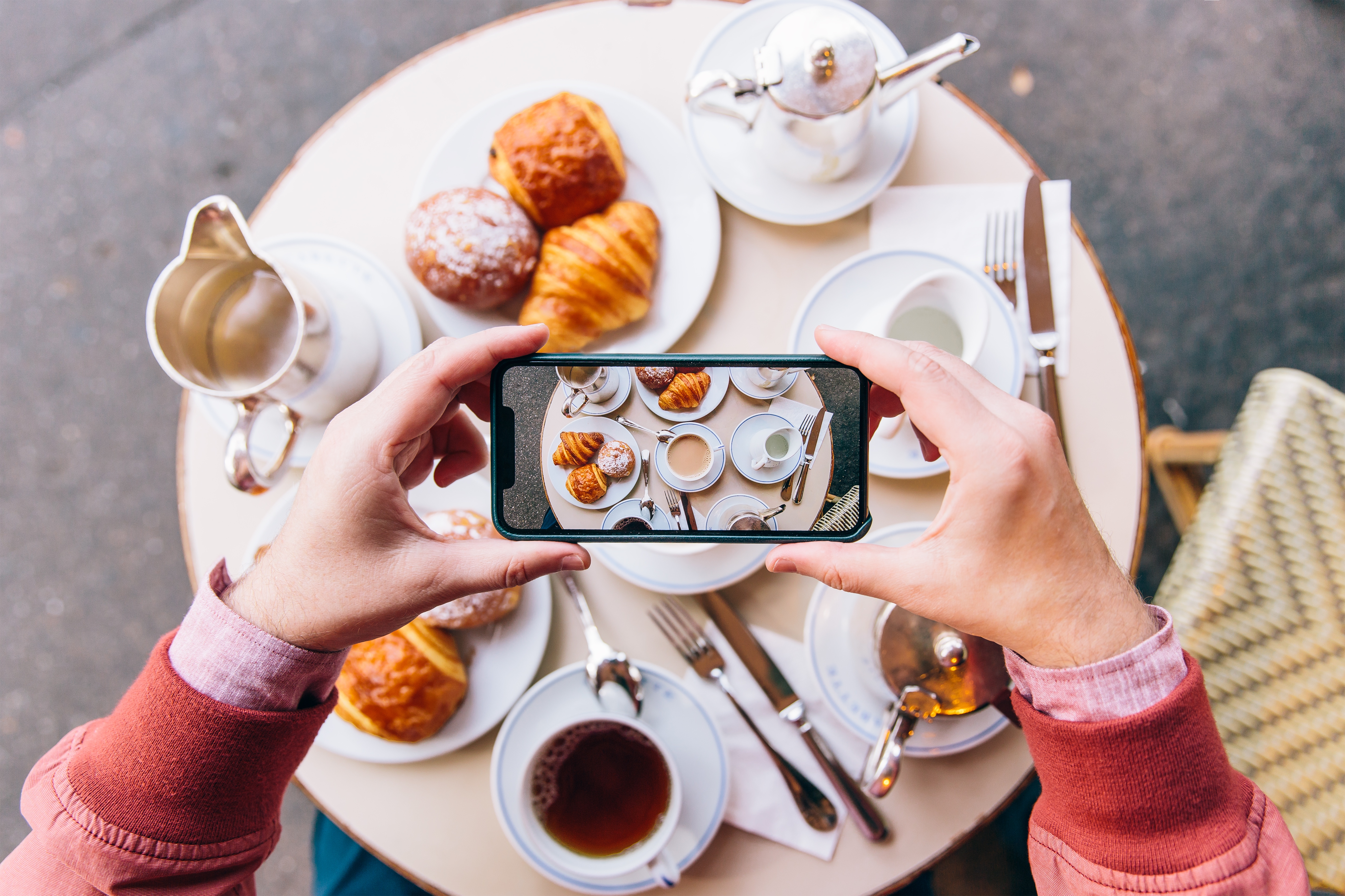 young man photographing French breakfast with croissants on the table in sidewalk cafe with smartphone in Paris, France