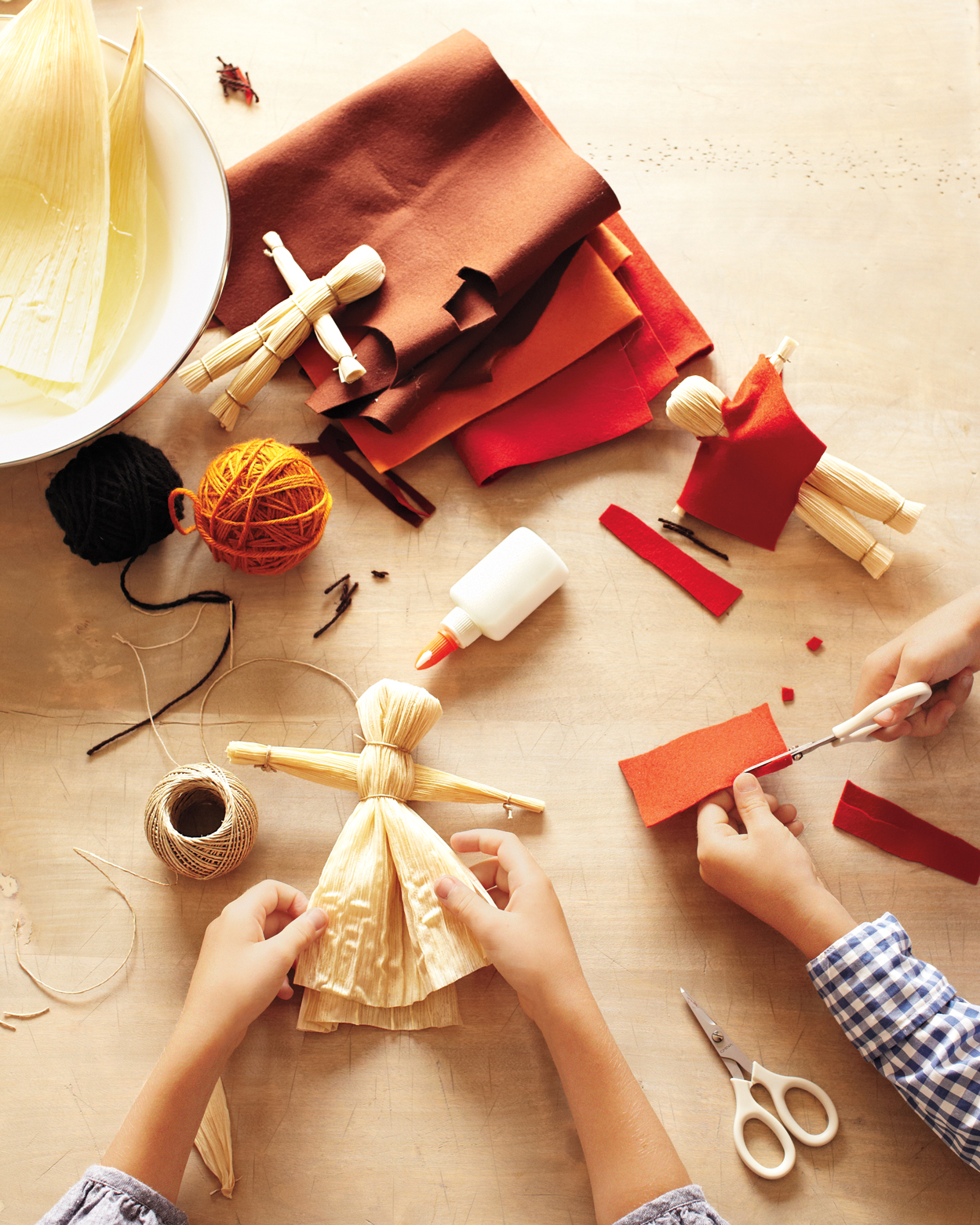 kids crafting cornhusk dolls for Thanksgiving