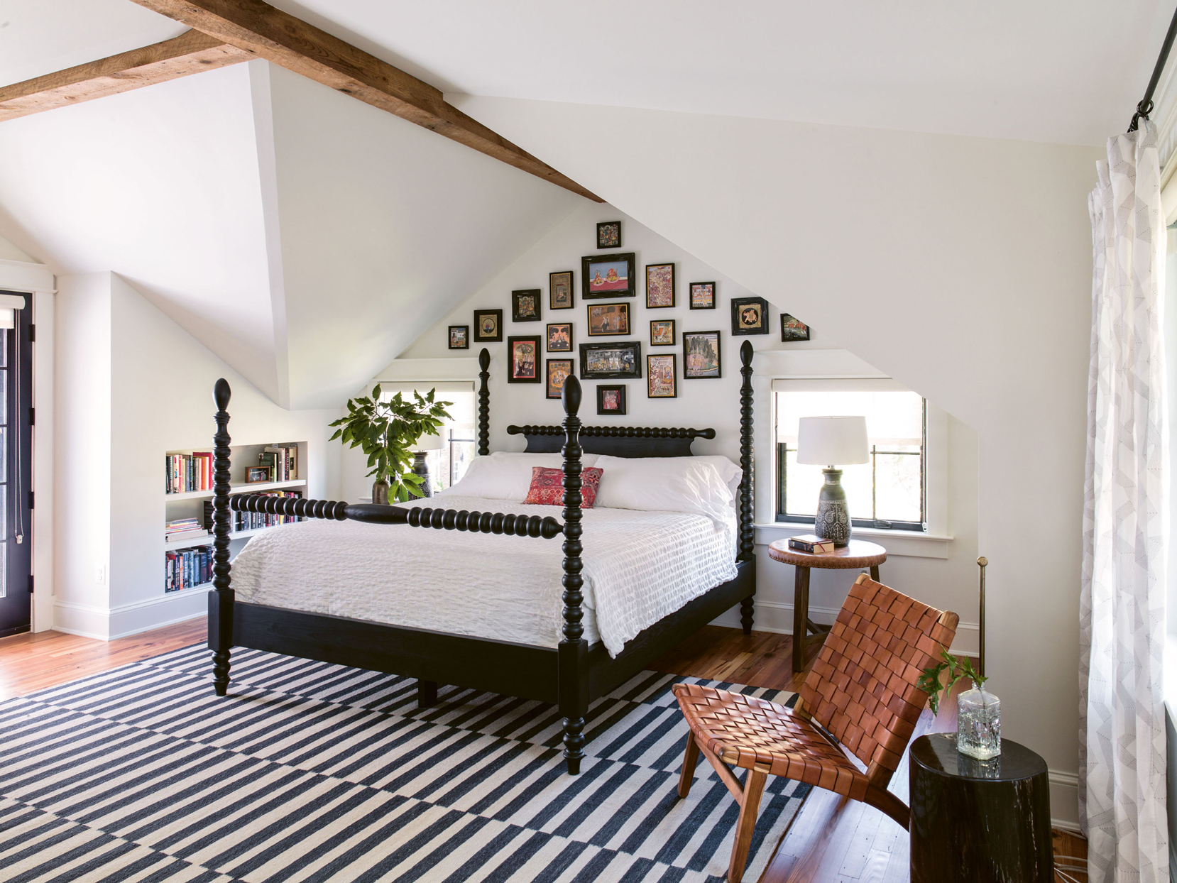 master bedroom with black spool bed and sloped ceilings