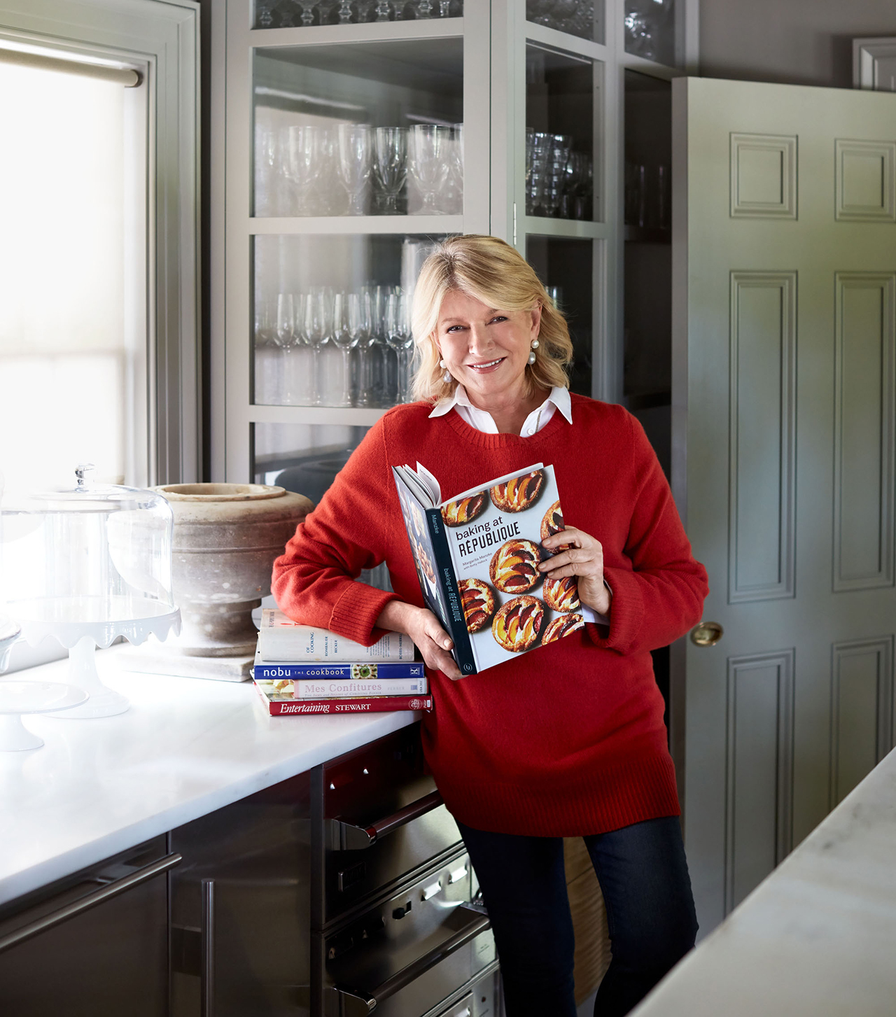 martha holding baking cook book in kitchen