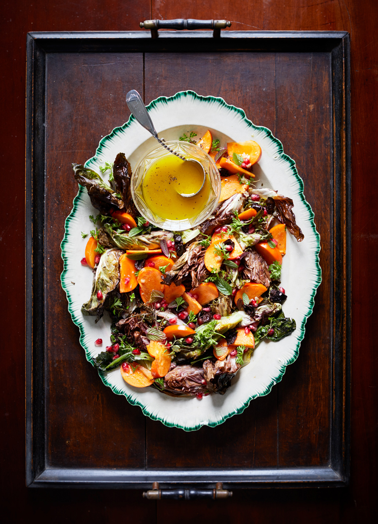 persimmons and roasted chicories with shallot vinaigrette served on a white plate