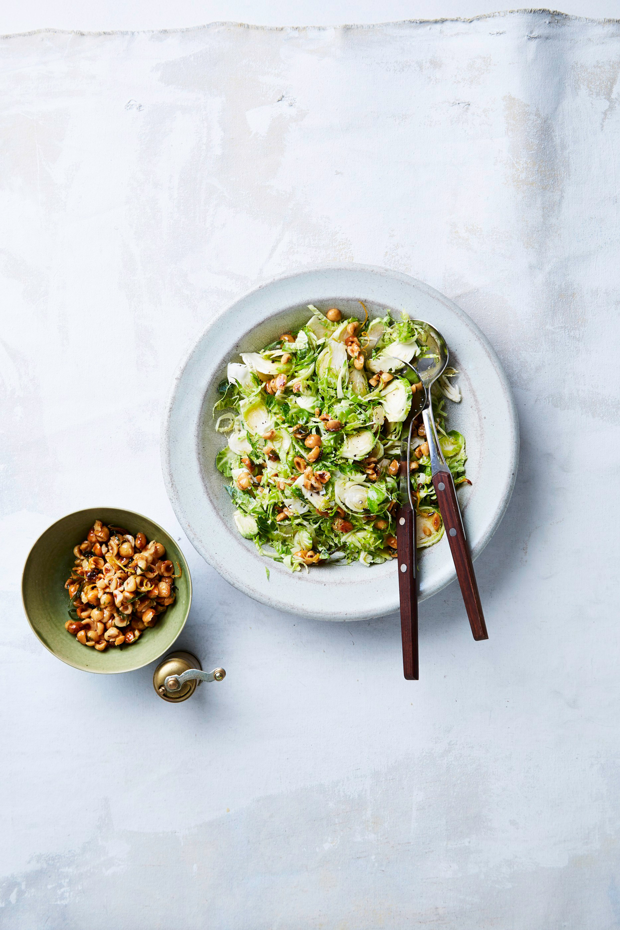 overhead view of shredded brussels sprout salad topped with hazelnut crunch