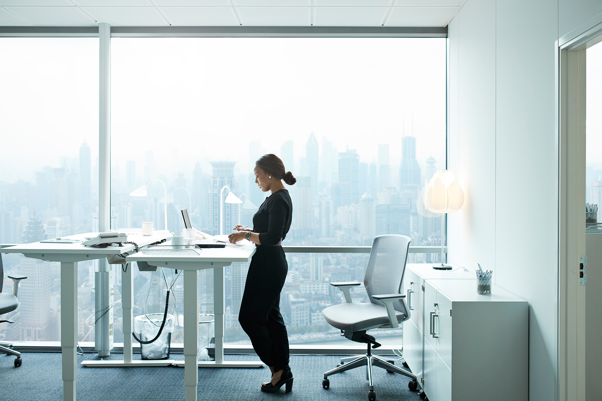 woman office standing desk large window