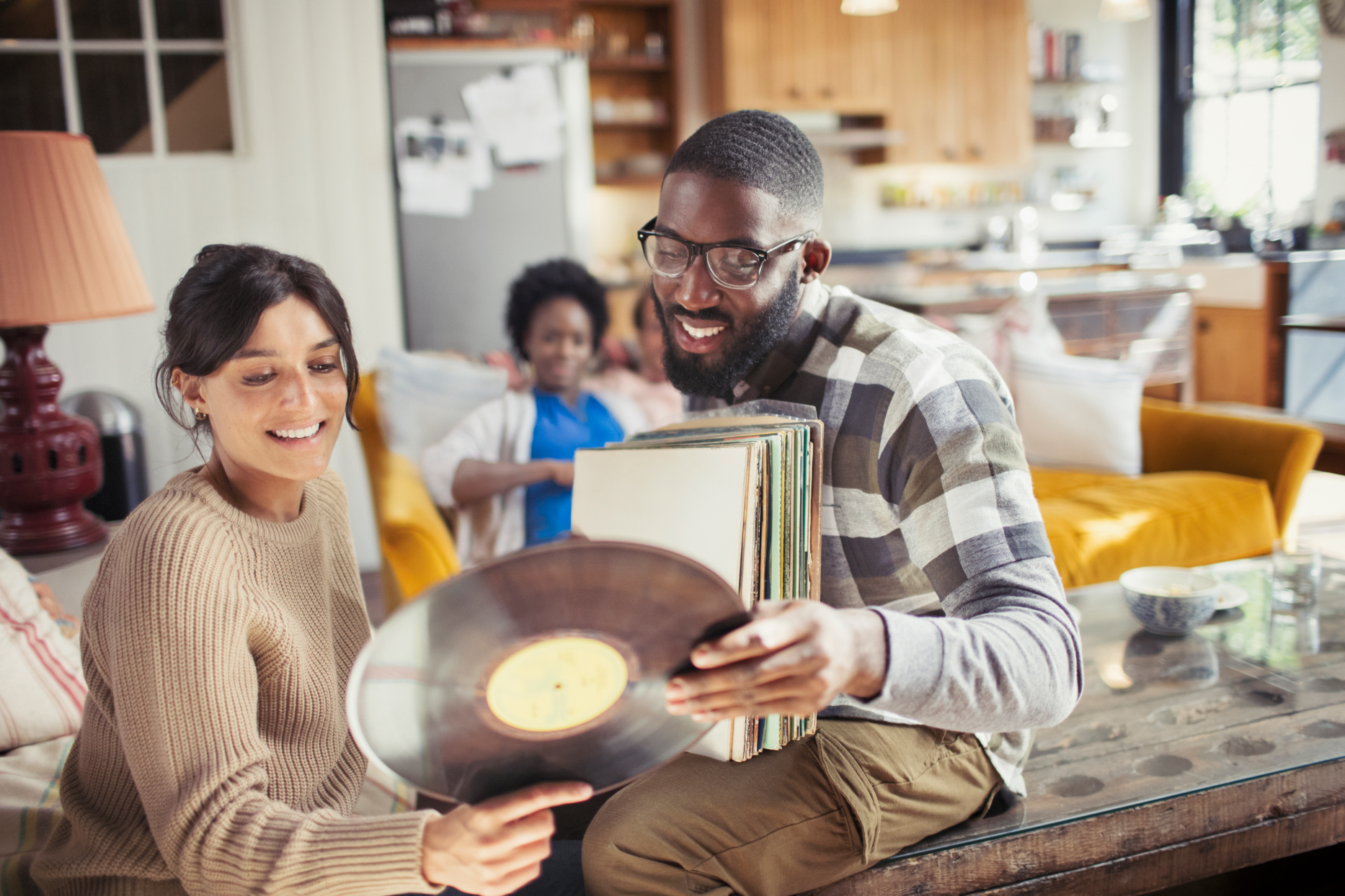 couple in living room holding vinyl record