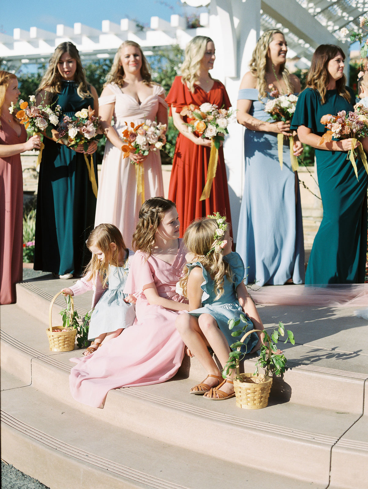 bridesmaids and flower girls in variety of colored dresses holding flowers