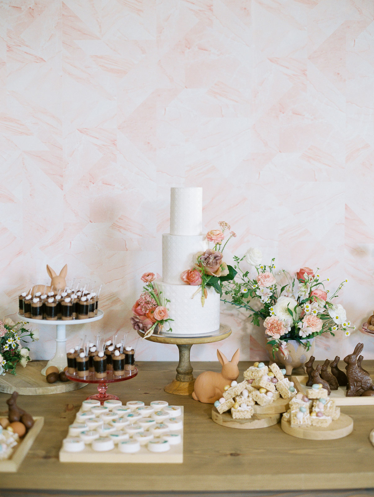 three tiered white wedding cake on dessert table with pink flowers