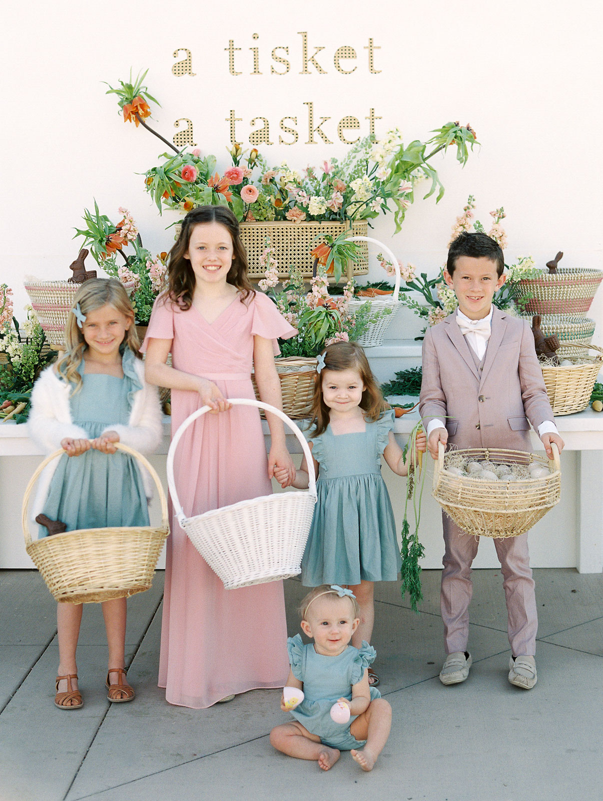 flower girls wearing pastel blue and pink outfits holding baskets