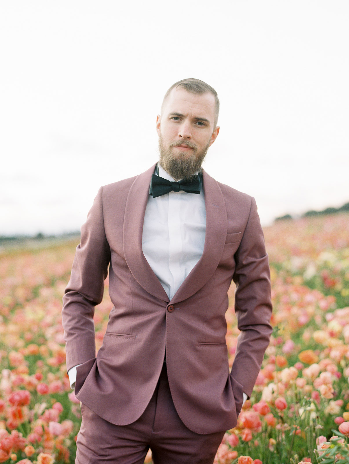 groom wearing mauve suit with black bow tie